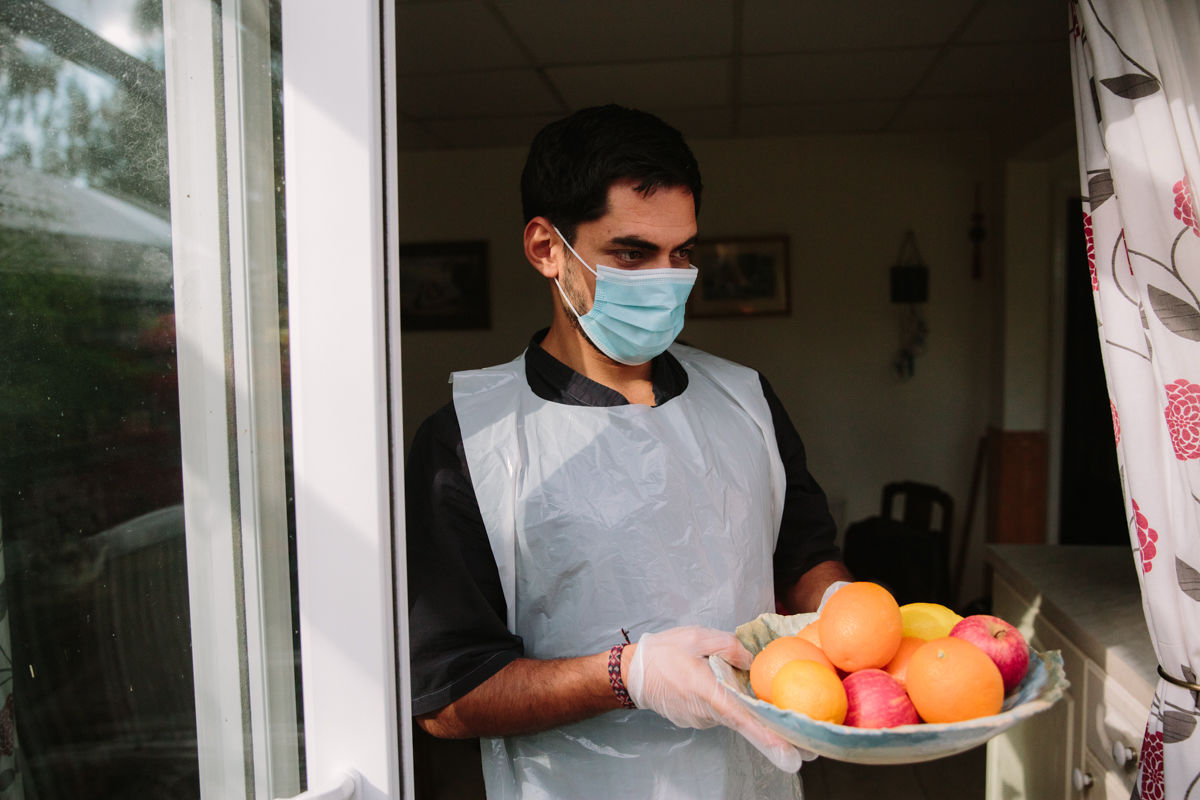 Man wearing a surgical mask and holding a bowl of fruit