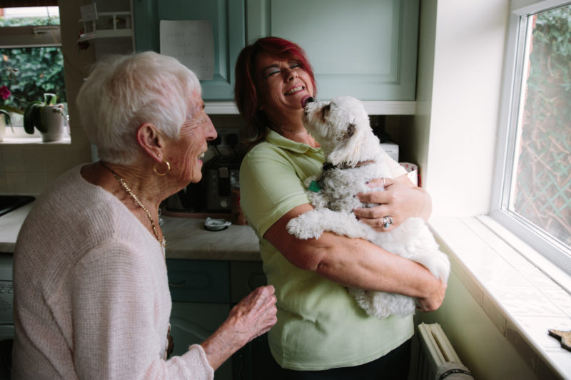 Woman smiling and holding a dog
