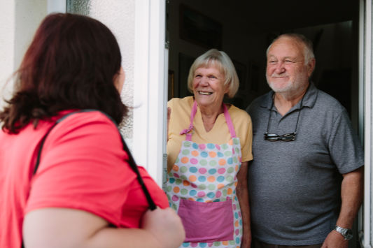 Elderly couple meeting a wellbeing worker at their door