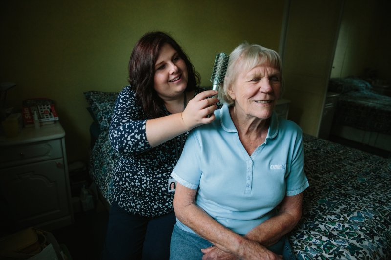 Well being support worker brushing Joan's hair