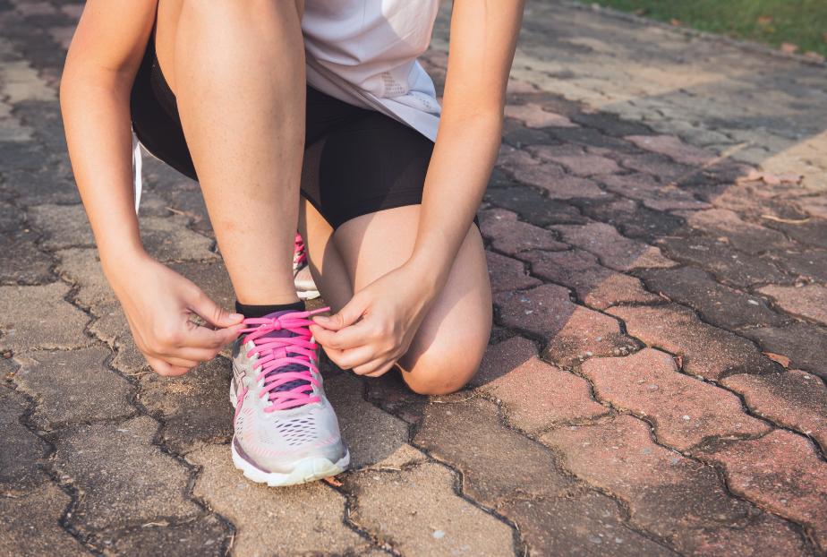Woman wearing running gear tying her shoelaces