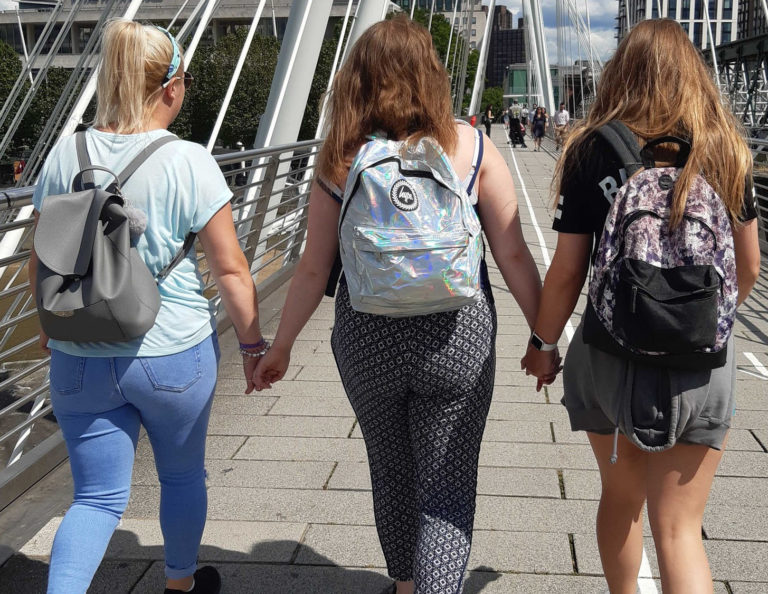 Three young women holding hands and walking across a bridge