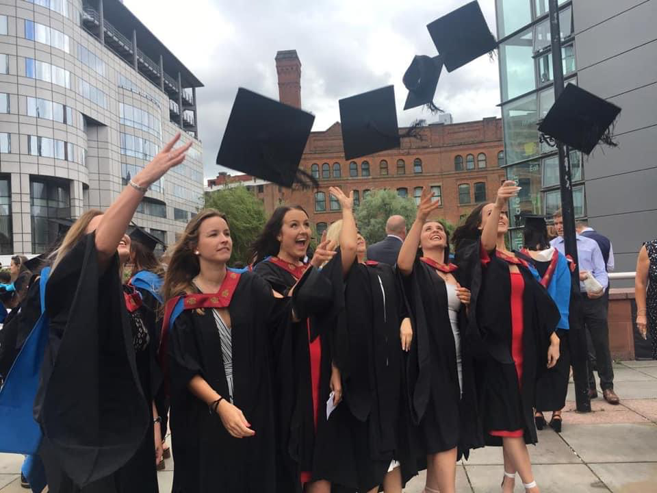Women in graduation gowns celebrating completeing their university courses