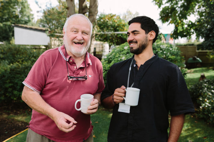 Two men drinking tea and having a laugh