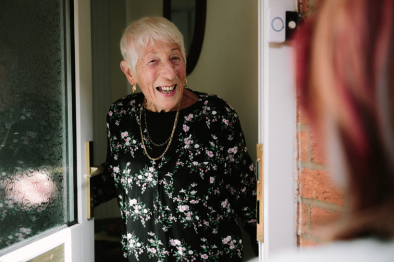 A woman welcoming a carer at her front door